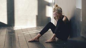 Крупный план молодого танцора девочка-подростка плача после представления потери сидит на поле в зале внутри помещения Стоковое фото RF