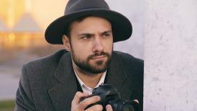 Крупный план молодого человека папарацци в шляпе фотографируя знаменитости на камере пока шпионка за стеной Стоковое Изображение