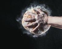Крупный план мужских рук положил свежий хлеб на черную предпосылку с космосом экземпляра для вашего текста Стоковые Фотографии RF