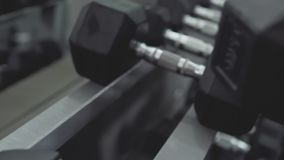 Крупный план мужской руки принимая гантели, тренажер прочности в спортзале акции видеоматериалы