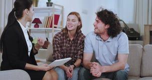 Крупный план на большой живущей комнате на агенте дома женщины софы привлекательном и ее клиент имеют прекрасное обсуждение около акции видеоматериалы
