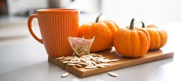 Крупный план на малых семенах и пакетике чая тыкв на таблице стоковая фотография