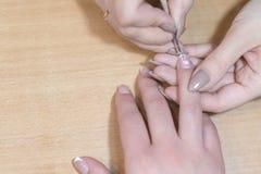 Крупный план ногтей картины beautician женского клиента Женщина в салоне курорта красоты делая маникюр Стоковая Фотография RF