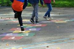Крупный план ног детей скача и играя классики в школе стоковое фото rf