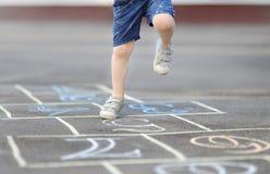Крупный план ног и классиков ` s мальчика нарисованный на асфальте Стоковые Фотографии RF