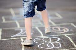 Крупный план ног и классиков ` s мальчика нарисованный на асфальте Стоковые Изображения