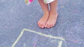 Крупный план ног и классиков ` s мальчика нарисованный на асфальте Ребенок играя игру классиков на спортивной площадке outdoors стоковые фото