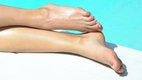 Крупный план ног красивой женщины представляя около бассейна, лосьона солнцезащитного крема видеоматериал