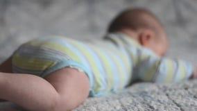Крупный план ног ` s младенца пробуя вползти лежащ на кровати сток-видео