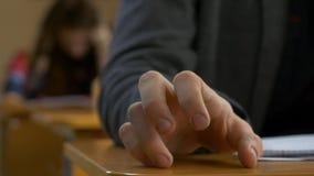 Крупный план пальца руки студента выстукивая Молодой человек выстукивает его пальцы на таблице стоковая фотография rf