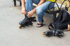 Крупный план парня человека кладя на коньки ролика внешние Стоковые Фото