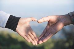 Крупный план пар делая форму сердца с руками, соединяет в любов, фокусе на руках, туристах человека и женщины в горах на заходе с стоковые фото