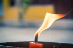 Крупный план пламени свечи в буддийском виске, blured предпосылке Стоковые Изображения