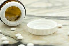 Крупный план планшет c много витаминов перед открытой бутылкой крышки в белой предпосылке стоковые изображения rf