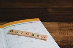 Крупный план плитки алфавита в ОКТЯБРЕ на календаре книги плановика на деревянном столе стоковая фотография rf