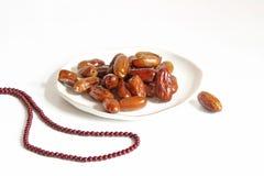 Крупный план плиты фарфора с плодоовощами даты и шариками молитве на белой таблице Поздравительная открытка для iftar и Рамазана Стоковая Фотография RF