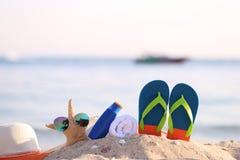 Крупный план пляжа лета с аксессуарами голубых темповых сальто сальто, шляпы, сливк предохранения от солнца, полотенца и солнечны стоковые фото