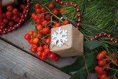 Крупный план подарка рождества на деревянной предпосылке с ветвями спруса, золы и красных шариков Стоковые Фото