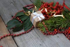 Крупный план подарка рождества на деревянной предпосылке с ветвями спруса, золы и красных шариков Стоковое Изображение