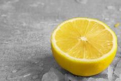 Крупный план половины суккулентного желтого лимона, частей льда и падений воды на свете - серый цвет запачкал предпосылку Стоковые Фото