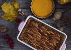 крупный план предпосылки осени красит красный цвет листьев плюща померанцовый Домодельная тыква, яблочные пироги на благодарение Стоковое фото RF