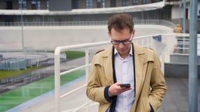 Крупный план привлекательного кавказского человека готовя стадион, проверяя его телефон и смотря прямо на камере с сток-видео