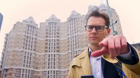 Крупный план привлекательного успешного кавказского человека смотря прямо на камере и указывая с пальцем на ем самомоднейше видеоматериал
