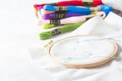 Крупный план процесса вышивки, зеленого потока в игле Деревянная рамка вышивки для needlework Рабочее место для Стоковое фото RF