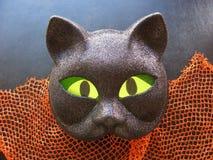 Крупный план пугающей маски черного кота хеллоуина с накаляя зелеными глазами Стоковые Изображения