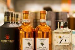 Крупный план различных брендов бутылок джина на супермаркете shelve стоковое фото rf