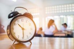 Крупный план ретро будильника с часами ` 10 o на учителе таблицы i Стоковые Фото
