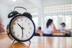 Крупный план ретро будильника с часами ` 10 o на учителе таблицы i Стоковая Фотография