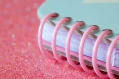 Крупный план розовой скрепленной спиралью тетради стоковое изображение