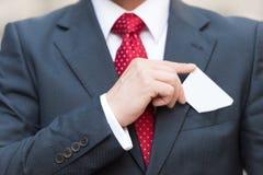 Крупный план руки бизнесмена держа белую визитную карточку над карманн костюма изолированным на белизне Бизнесмен в костюме и кра стоковое изображение rf