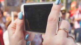 Крупный план руки женщины делая видео на мобильном телефоне во время торжества дня победы видеоматериал