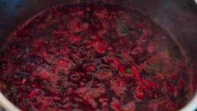 Крупный план руки женщины смешивает кипя суп бураков в баке видеоматериал