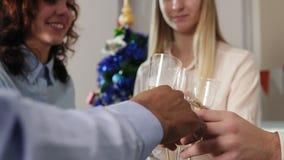 Крупный план: руки многонациональной группы в составе работники офиса clinking стекла с шляпами рождества игристого вина нося во  акции видеоматериалы