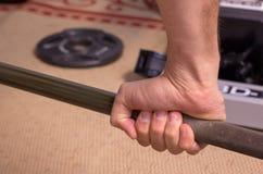 Крупный план руки ` s человека держа штангу стоковые фото