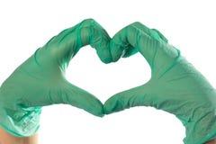 Крупный план рук в зеленых перчатках латекса Сердце сложено от рук стоковая фотография