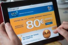 Крупный план рук женщины на домашней странице банка Credit Lyonnais французской вебсайта на таблетке Стоковое Изображение RF