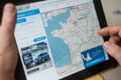 Крупный план рук женщины на домашней странице вебсайта трассы карты Michelin на таблетке Стоковая Фотография RF