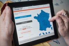 Крупный план рук женщины на домашней странице монетки Le bon француза использовал вебсайт продажи на таблетке Стоковые Фотографии RF