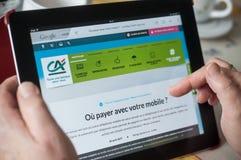 Крупный план рук женщины на домашней странице agricole кредита вебсайта на таблетке Стоковая Фотография