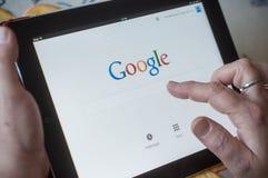 Крупный план рук женщины на поиске домашней страницы Google вебсайта на таблетке Стоковая Фотография RF