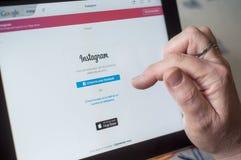 Крупный план рук женщины на регистрации домашней страницы Instagram вебсайта на таблетке Стоковые Изображения RF