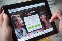 Крупный план рук женщины на meetic домашней странице датировка вебсайта на таблетке Стоковое Изображение