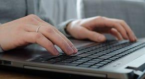 Крупный план рук молодого человека при кольцо замужества печатая на клавиатуре Стоковое Фото