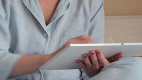 Крупный план рук молодой женщины в голубом pyjama дома и печатать акции видеоматериалы