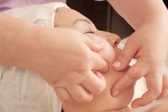 Крупный план рук beautician делает массаж подбородка к женщине Masseur отжимает его пальцы на женской стороне стоковая фотография rf