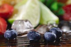 Крупный план свежей суккулентной голубики, кубов льда, известки, лимонов и клубник на красочной запачканной предпосылке стоковое фото rf